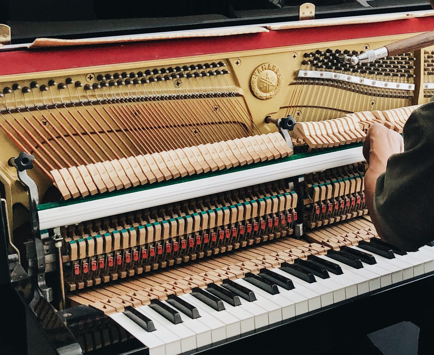 Piano tuner tuning an upright piano